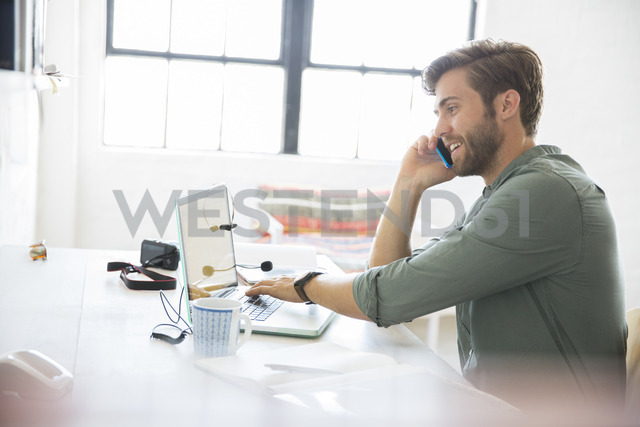 Portrait of young man sitting at desk with mobile phone and laptop - CAIF13310