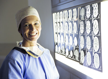 Portrait of smiling surgeon reviewing MRI scans - CAIF13319
