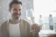 Portrait smiling man drinking white wine in restaurant - CAIF13361