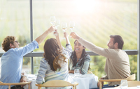 Friends toasting wine glasses overhead at winery dining room table - CAIF13370