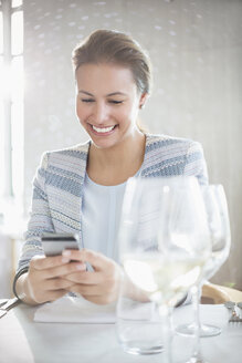 Smiling woman texting with cell phone at restaurant table - CAIF13382