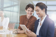 Smiling businesswomen using digital tablet in office - CAIF13388