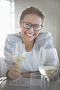Portrait confident woman with eyeglasses drinking white wine - CAIF13394