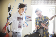 Two teenage boys having fun and playing electric guitar in room - CAIF13418