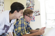 Two teenage boys having fun while using digital tablet in room - CAIF13421