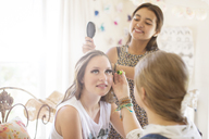 Three teenage girls doing make-up and brushing hair in bedroom - CAIF13436