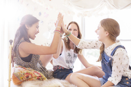 Three teenage girls doing high five on bed - CAIF13451