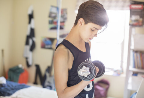 Teenage boy exercising with dumb bell - CAIF13454