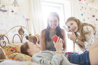 Three teenage girls listening to music from smartphone in bedroom - CAIF13457