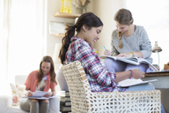 Three teenage girls doing homework in room - CAIF13463