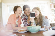 Three teenage girls looking at photograph while sitting at table - CAIF13466