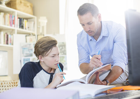 Father helping teenage son with his homework - CAIF13469
