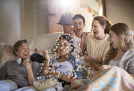 Group of teenagers throwing popcorn on themselves while sitting on sofa - CAIF13478