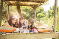 Three teenage girls reading magazine while lying in tree house in summer - CAIF13481