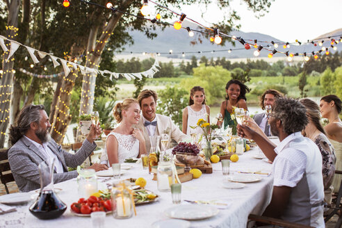 Young couple and their guests sitting at table during wedding reception in garden - CAIF13487