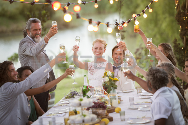 Young couple and their guests toasting with champagne during wedding reception in garden - CAIF13490