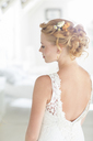 Young bride standing in sunny bedroom - CAIF13496