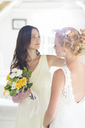 Bridesmaid helping bride with hairstyle in bedroom - CAIF13499