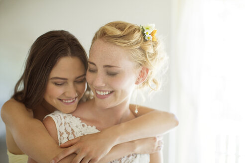 Bridesmaid embracing bride in bedroom - CAIF13505