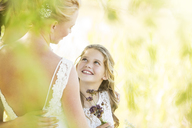 Smiling bridesmaid with flowers and bride during wedding reception in garden - CAIF13508