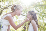 Bride and bridesmaid facing each other in domestic garden during wedding reception - CAIF13523