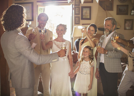 Young couple and guests toasting with champagne at wedding reception - CAIF13529