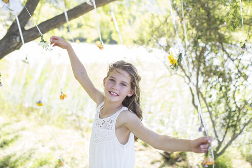 Smiling bridesmaid playing with decorations in domestic garden during wedding reception - CAIF13535