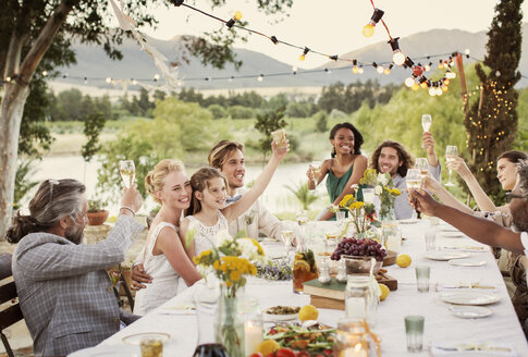 Young couple and guests toasting with champagne during wedding reception in domestic garden - CAIF13544