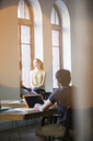 Lens flare over smiling businesswomen talking in office window - CAIF13613