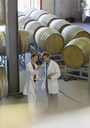 Vintners in lab coats examining wine in winery cellar - CAIF13622