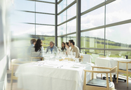 Friends sitting at table in sunny winery dining room - CAIF13691