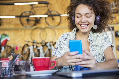 Smiling woman with headphones texting on cell phone in bike shop - CAIF13709