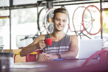 Smiling man drinking coffee at laptop in bike shop - CAIF13712