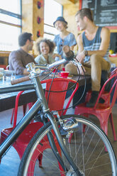 Friends hanging out at cafe behind bicycle - CAIF13718