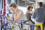 Smiling woman texting with cell phone at railing above bicycle - CAIF13721