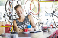 Portrait smiling man with coffee and cell phone in bicycle shop - CAIF13727