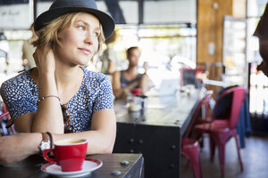 Pensive woman in hat with coffee looking away in cafe - CAIF13733