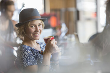 Portrait smiling woman in hat drinking espresso in cafe - CAIF13736