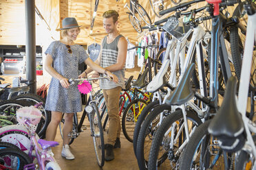 Couple eyeing bicycle in bicycle shop - CAIF13739