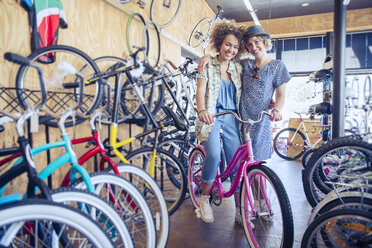 Portrait smiling women hugging with bicycle in bicycle shop - CAIF13745