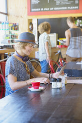Woman in hat using digital tablet at cafe - CAIF13751