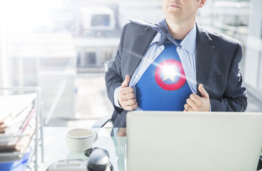 Businessman opening shirt to reveal superhero costume - CAIF13760
