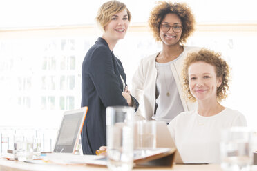 Portrait of smiling office workers sitting at desk - CAIF13766