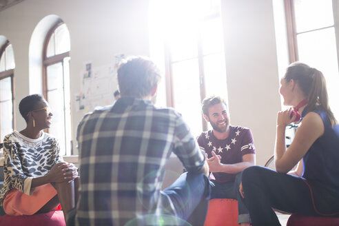 Casual business people meeting in circle in sunny office - CAIF13841