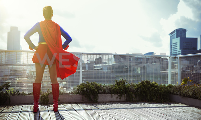 Superhero standing on city rooftop - CAIF13928
