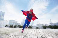 Superhero running with cape on city rooftop - CAIF13931