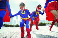 Family of superheroes running on city rooftop - CAIF13934