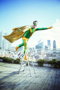 Superhero posing on stepladder on city rooftop - CAIF13937