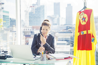Businesswoman working with superhero costume hanging in office - CAIF13940
