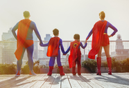 Superhero family standing on city rooftop - CAIF13943